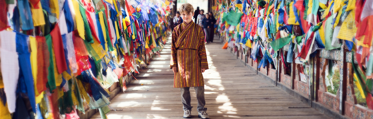 Young boy walking on a bridge in Bhutan lined with prayer flags