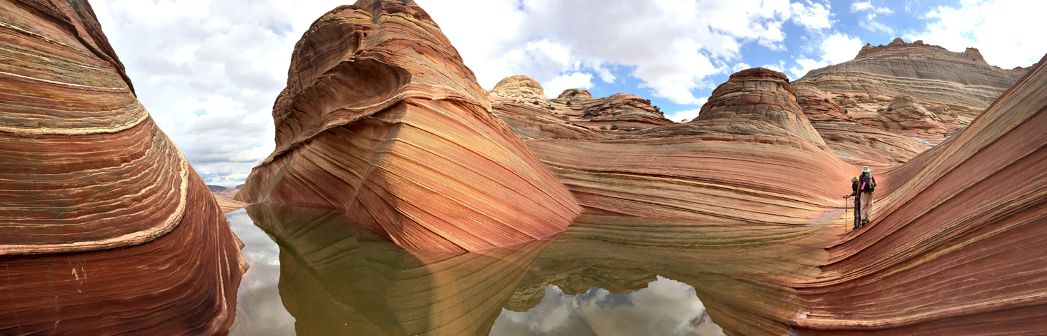 Two hikers in Coyote Buttes. The Coyote Buttes area, on the Utah/Arizona border, is most popular for a multi-colored sandstone rock formations.