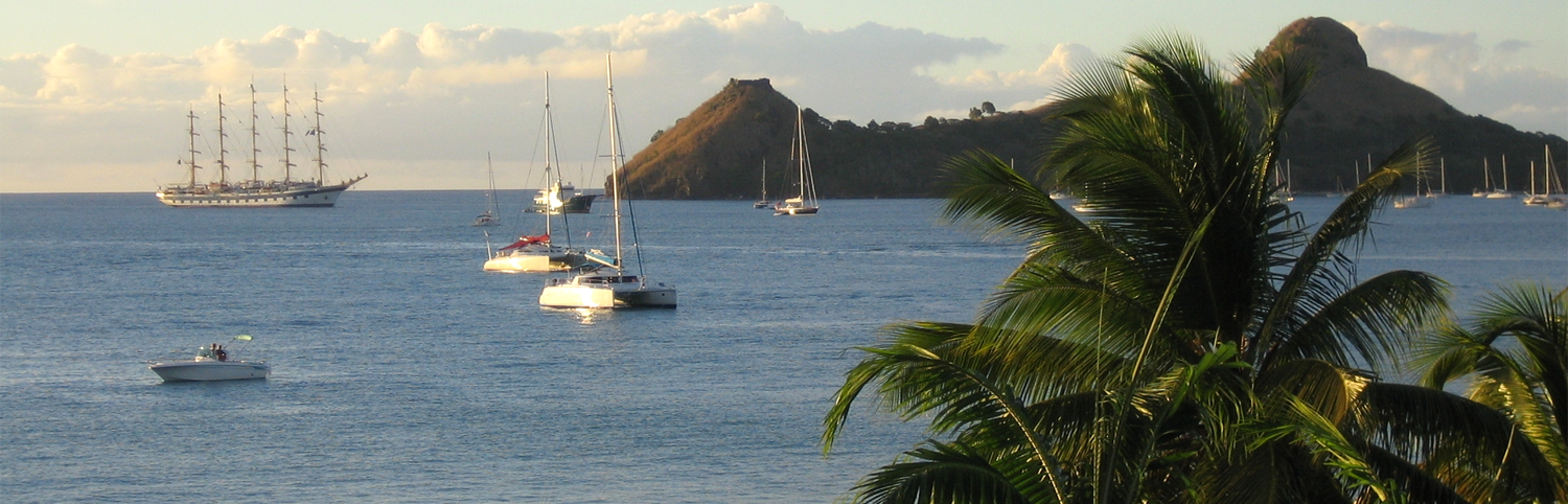 View of a great expanse of ocean with sail boats taken from the shores of Saint Lucia
