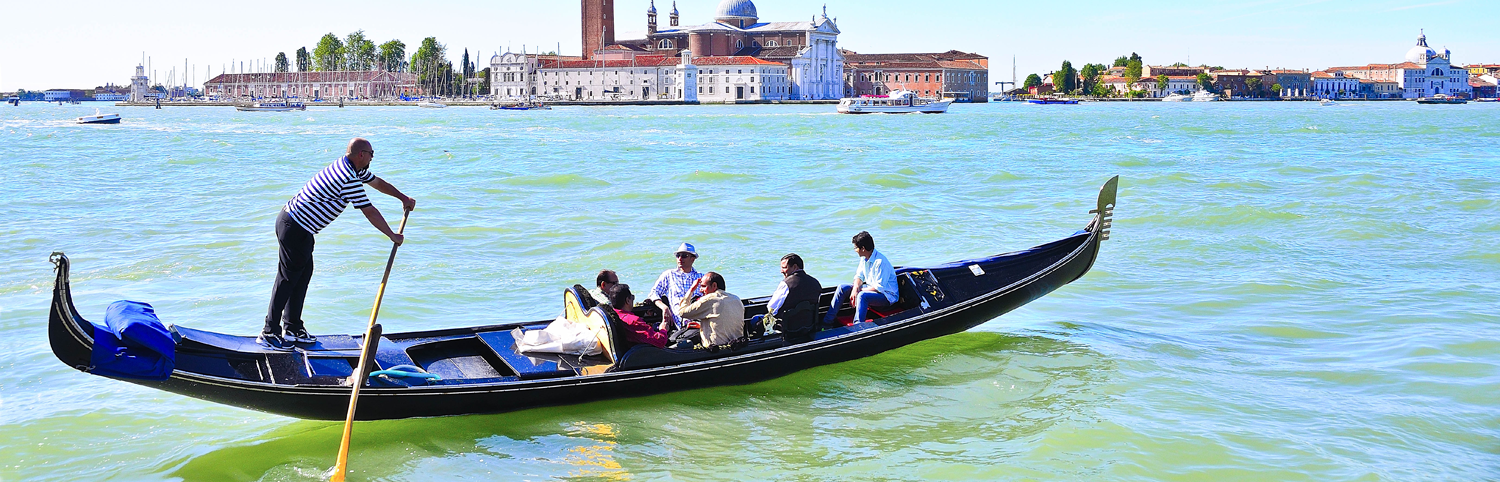 5 people on a gondola flotilla ride in Venice